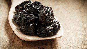 Prunes in a wooden spoon